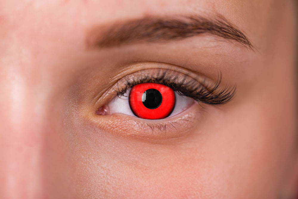 woman wearing red vampire contact lenses